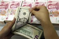 China's central bank said it would widen the yuan's trading band against the dollar from 0.5 percent to 1.0 percent, loosening its grip on the Asian giant's tightly controlled currency