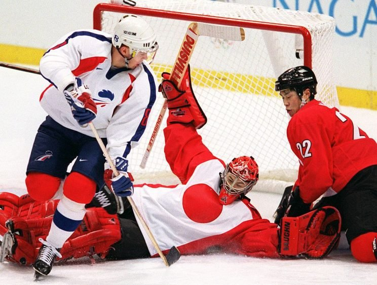 French forward Arnaud Briand (L) looks on as Japanese goalkeeper Dusty Imoo falls onto teammate Makoto Kawahira (R) during their men preliminary match at the Nagano Winter Olympics 09 February. The match is at a 2-2 draw in the third period. AFP PHOTO/ROBERT SULLIVAN / AFP / ROBERT SULLIVAN (Photo credit should read ROBERT SULLIVAN/AFP/Getty Images)