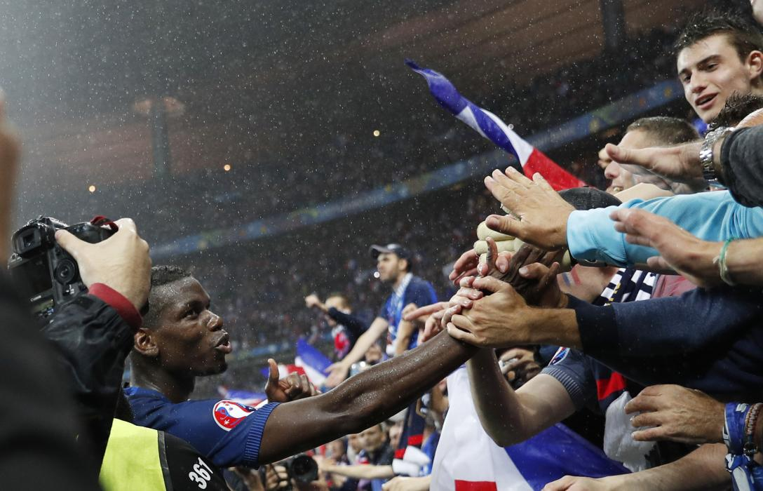 France's Paul Pogba celebrates with fans after the game