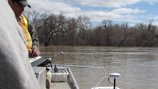 In this April 30, 2013 photo, a device called an acoustic Doppler current profiler is tethered to the side of a boat and used to take stream flow measurements and river depth readings on the Red River in Fargo, N.D. Even with reams of data, forecasting a flood is still an imprecise science. (AP Photo/Dave Kolpack)