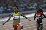 Ethiopia's Meseret Defar (L) celebrates as she wins the gold medal in the women's 5000m final at the athletics event of the London 2012 Olympic Games on August 10, 2012 in London