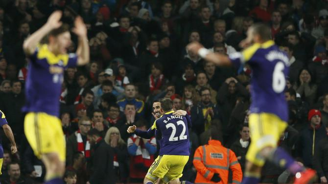 Swansea City players celebrate after an Arsenal own goal during their English Premier League soccer match at the Emirates stadium in London