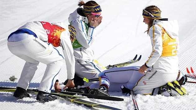 Sweden's Charlotte Kalla lies on the ground surrounded by team mates after winning gold