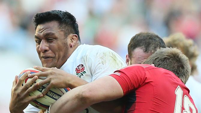 England's Mako Vunipola. left, is grappled by Wales's Rhodri Jones during the Six Nations Rugby Union match between England and Wales at Twickenham stadium in London Sunday, March, 9, 2014. (AP Photo/Alastair Grant)