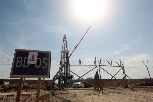 A Gazprom security man walks behind a fence at a drilling platform at an oilfield near the Iraqi city of Badra, south of Baghdad, on October 18, 2012. The World Bank announced a $900 million support plan for Iraq aimed at helping the war-ravaged country better manage its human and vast oil resources.