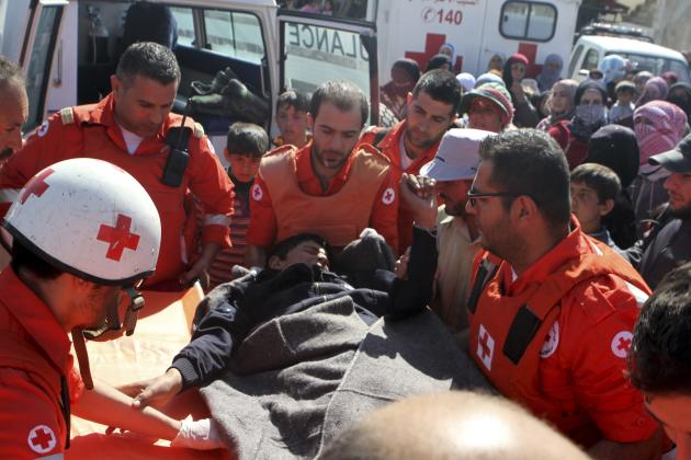 Lebanese Red Cross members help a wounded man in Tfail village near the Syrian border