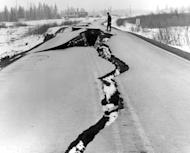 In this March 27, 1964 photo released by the U.S. Geological Suvery, a man looks over fissures following an earthquake in the Seward Highway at the head of Turnagain Arm near Anchorage, Alaska. North America's largest earthquake rattled Alaska 50 years ago, killing 15 people and creating a tsunami that killed 124 more from Alaska to California. The magnitude 9.2 quake hit at 5:30 p.m. on Good Friday, turning soil beneath parts of Anchorage into jelly and collapsing buildings that were not engineered to withstand the force of colliding continental plates. (AP Photo/U.S. Geological Survey