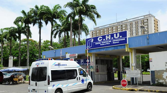 A TV crew is waiting outside the hospital where French singer Johnny Hallyday is hospitalized in Pointe a Pitre, Guadeloupe, French Antilles, Monday Aug. 27, 2012. Johnny Hallyday, the French entertainer famed for his Elvis-like style and gravelly voice, was hospitalized for a severe case of bronchitis, his producer said Monday. (AP Photo/Dominique Chomereau-Lamotte)