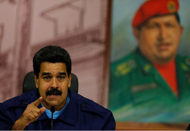 Venezuela's President Nicolas Maduro speaks next to a painting of the late Hugo Chavez, during a news conference at Miraflores Presidential Palace in Caracas, Venezuela, Friday, Feb. 21, 2014. Spe