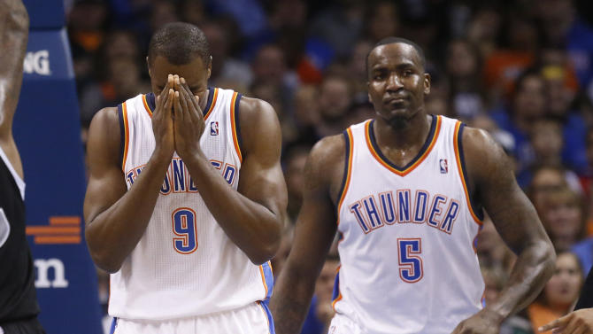 Oklahoma City Thunder forward Serge Ibaka (9) reacts after being called for offensive interference in the second quarter of an NBA basketball game against the Sacramento Kings in Oklahoma City, Sunday, Jan. 19, 2014. Thunder center Kendrick Perkins (5) looks on. (AP Photo/Sue Ogrocki)
