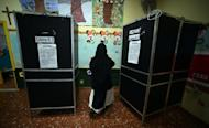 A nun gets ready to vote at a polling station in downtown Rome on February 24, 2013. Italy on Monday holds a second day of voting in a critical election for the future of the eurozone in which the centre-left Democratic Party is expected to win but fall short of a governing majority