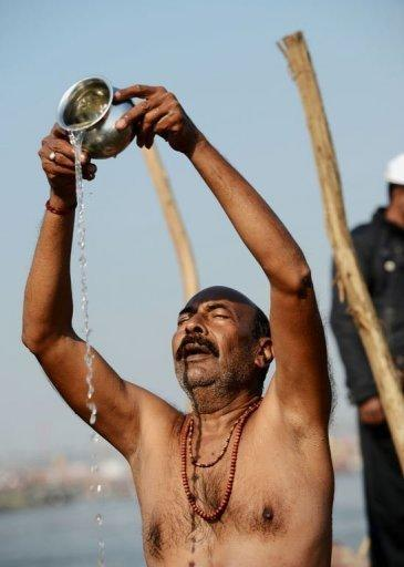 A Hindu devotee prays on the banks of the River Ganges during the Kumbh Mela in Allahabad, on February 9, 2013