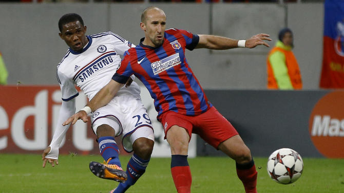 Chelsea's Samuel Eto'o, left, takes a shot at goal next to Steaua's Iasmin Latovlevici, rift, during the soccer Champions League group E match between Steaua Bucharest and Chelsea in Bucharest, Romania, Tuesday, Oct. 1, 2013