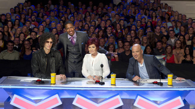 "In this April 2012 photo released by NBC, host Nick Cannon, standing, poses with judges, seated from left, Howard Stern, Sharon Osbourne and Howie Mandel from the talent competition series ""America's Got Talent,"" during auditions in Tampa, Fla. A prime-time display of artistic and athletic talent has carried NBC to the top of the television ratings. The Nielsen company says NBC was last week's most popular network. Three editions of ""America's Got Talent"" on Monday, Tuesday and Wednesday, June 25-27, were the three most-watched shows.  (AP Photo/NBC, Virginia Sherwood)"
