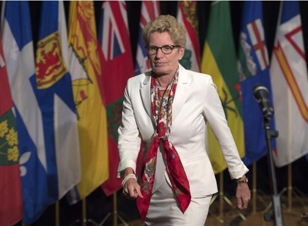 Ontario Premier Kathleen Wynne heads away from the microphone after talking with reporters at the summer meeting of Canada's premiers in St. John's on Thursday, July 16, 2015. THE CANADIAN PRE