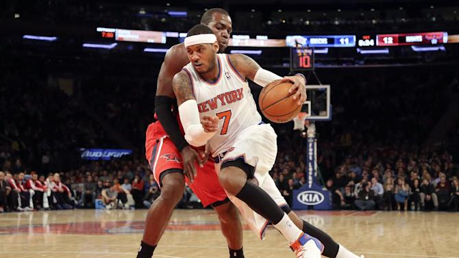 New York Knicks forward Carmelo Anthony (7) drives to the basketball against Atlanta Hawks forward Paul Millsap during the first half of an NBA basketball game Saturday, Dec. 14, 2013, in New York
