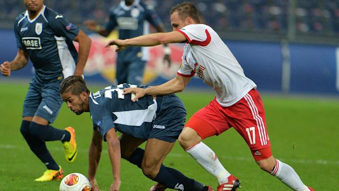 Salzburg's Andreas Ulmer, right, and Standard's Mehdi Carcela-Gonzalez challenge for the ball  during the Europa League group C soccer match  between Red  Bull Salzburg and Standard Liege  in Salzburg , Austria,  Thursday Oct. 24, 2013