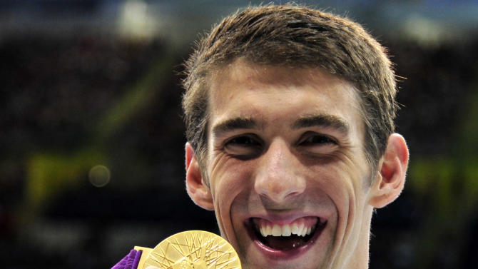 Michael Phelps of the U.S. celebrates with his gold medal at the men's 100m butterfly victory ceremony at the London 2012 Olympic Games at the Aquatics Centre