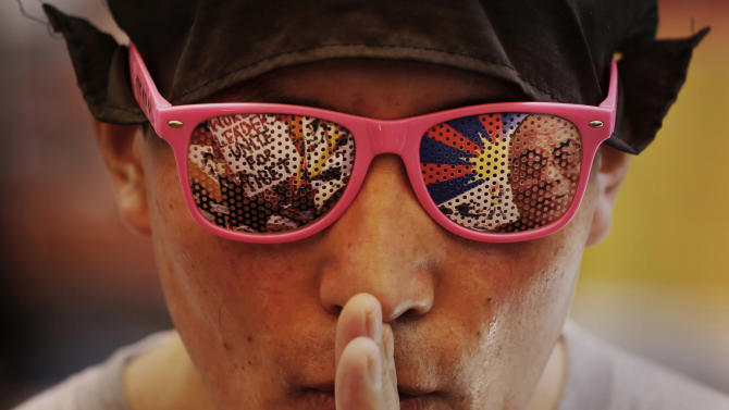 An exiled Tibetan man wearing glasses with a likeness of the Dalai Lama prays during a protest at a local neighborhood after they were stopped from protesting near the venue where Chinese Premier Li Keqiang was attending a meeting, in New Delhi, India, Monday, May 20, 2013. Li said Monday he chose India for his first foreign visit because cooperation between the world's two most populous nations is crucial to world stability and economic growth. He was visiting India just weeks after the two nations resolved a tense standoff between their troops over the disputed Himalayan border between their two countries. (AP Photo/Kevin Frayer)