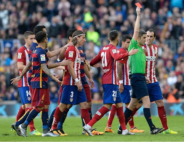 Atletico Madrid's defender Filipe Luis (2ndL) looks dejected after he was shown a red card during the Spanish league football match FC Barcelona vs Club Atletico de Madrid at the Camp Nou stadium
