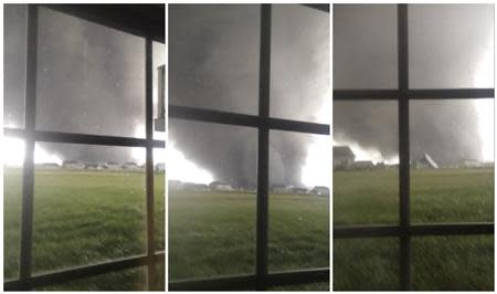 Combination of three video stills shows an active tornado as it touches down in Washington, Illinois