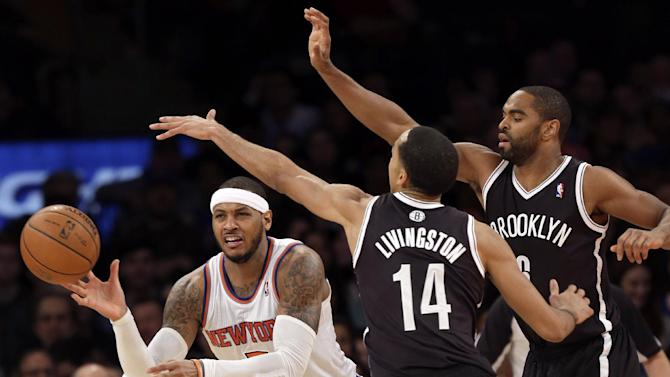 New York Knicks' Carmelo Anthony, left, passes while being defended by Brooklyn Nets' Alan Anderson, right, and Shaun Livingston during the second half of the NBA basketball game at Madison Square Garden, Monday, Jan. 20, 2014, in New York. The Nets defeated the Knicks 103-80