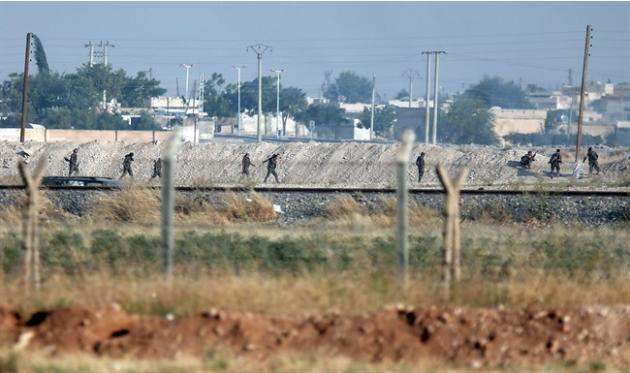 FILE-In this Monday, June 15, 2015 file photo taken from the Turkish side of the border between Turkey and Syria, in Akcakale, southeastern Turkey, showing Kurdish fighters with the Kurdish People&#39