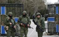 Armed men, believed to be Russian servicemen, stand guard outside the naval headquarters after it was taken over by pro-Russian forces in Sevastopol, March 19, 2014. REUTERS/Vasily Fedosenko