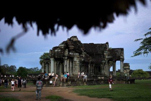 Tourists visit Angkor Wat temple during sunrise in Siem Reap, Cambodia, on July 14, 2012. A lost medieval city that thrived on a mist-shrouded mountain 1,200 years ago has been discovered by archaeologists in the Siem Reap region