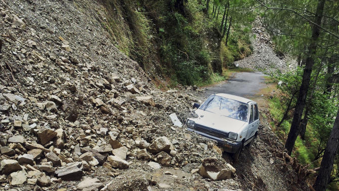 A car is abandoned in rubble from a landslide in Tehri, the northern Indian state of Uttarakhand, India, Wednesday, June 19, 2013. A joint army and air force operation evacuated nearly 12,000 Hindu pilgrims stranded in a mountainous area by torrential monsoon rains and landslides in northern India, but nearly 63,000 people remain cut off, a senior official said Wednesday. (AP Photo)