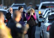 Residents grieve at the scene of a school shooting in Newtown, Connecticut. A young gunman slaughtered 20 small children and six teachers on Friday after walking into the school in an idyllic town with at least two sophisticated firearms