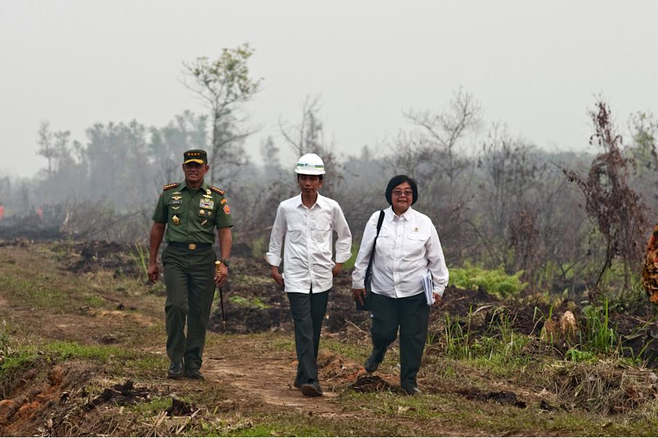 Indonesia President Widodo walks with TNI chief General Nurmantyo and Environment and Forestry Minister Nurbaya as they review the handling of forest fires at the Long Rimbo village in Kampar regency