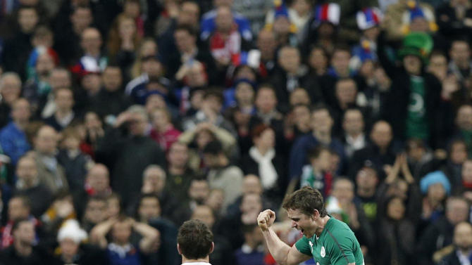 Ireland's rugby team players, right, celebrate after defeating France and winning the Six Nations Rugby Union tournament at the Stade de France stadium, in Saint Denis, outside Paris, Saturday, March 15, 2014. (AP Photo/Christophe Ena)