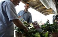 US President Barack Obama (C) buys a dozen ears of corn at the Bergman Orchards Farm Market in Port Clinton, Ohio. Obama Thursday heralded his first re-election campaign bus tour with a new trade blast at China and fresh accusations his White House foe Mitt Romney helped send US jobs abroad