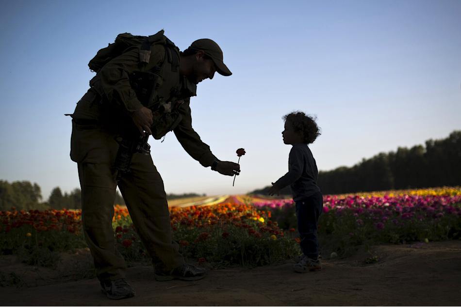 An Israeli soldier hands a buttercup flower to a child in a field in southern Israel, just outside the Gaza Strip