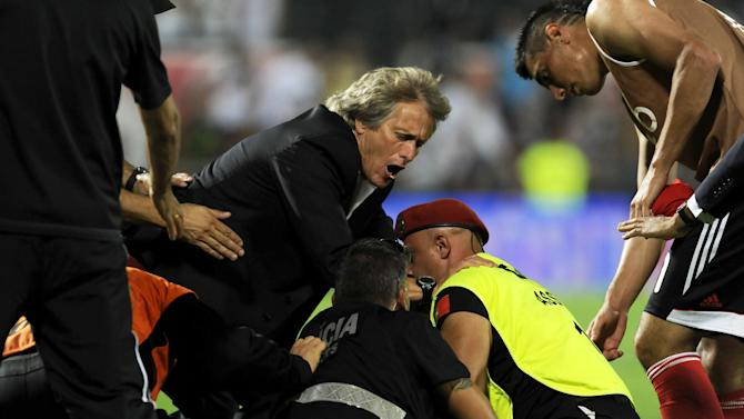 Benfica's coach Jorge Jesus, left, tries to stop a fan being arrested by the police after a pitch invasion during  the Portuguese League soccer match against Vitoria Guimaraes at D. Afonso Henrique stadium in Guimaraes, Portugal, Sunday, Sept. 22, 2013. Oscar Cardozo, right, scored the only goal in Benfica's 1-0 victory