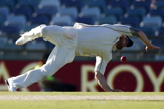 New Zealand captain Brendon McCullum dives but fails to stop a shot by Australia's captain Steve Smith during the fourth day of the second cricket test match at the WACA ground in Perth