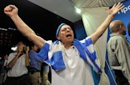 A New Democracy (ND) party supporter celebrates as he watches exit polls at the party's main election campaign booth in Athens on June 17, 2012. Greece's two main pro-bailout parties clinched enough votes to form a government in a cliffhanger election on Sunday, easing fears the country will crash out of the euro