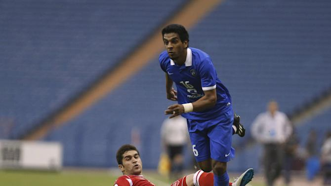 Yousef Al-Salem of Saudi Arabia's Al Hilal fights for the ball with Babak Hatami of Iran's Persepolis  during their AFC Champions League soccer match at King Fahd stadium in Riyadh