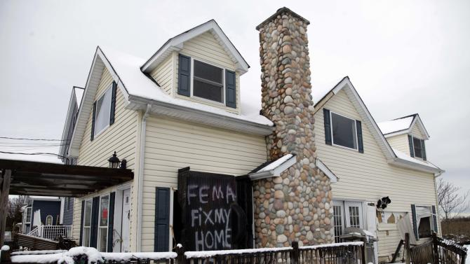 A sign is displayed on a house damaged by Superstorm Sandy in the Oakwood Beach section of Staten Island, New York, Thursday, Nov. 8, 2012. (AP Photo/Seth Wenig)