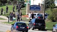 Law enforcement personnel walk outside the Sikh Temple of Wisconsin after a gunman burst into the temple with a 9mm handgun and several magazines of ammunition and opened fire on worshippers attending a Sunday service, authorities said