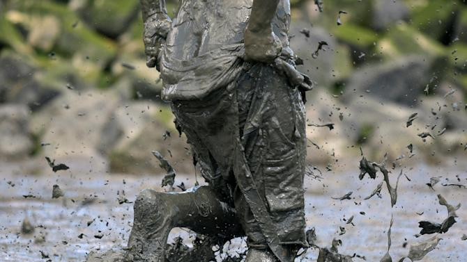 "A participant holds his pant during a handball match at the so called ""Wattoluempiade"" (Mud Olympics) in Brunsbuettel"