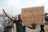 "A man carries placard reading, ""Jonathan And His Government Must Go!"" at Gani Fawehinmi Park in Lagos. Tens of thousands of protesting Nigerians defied an order to end a three-day-old strike Wednesday as unions threatened oil production and a mob rampaged in one city, leaving a police officer dead"