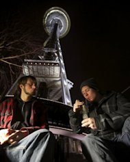 Dustin, left, and Paul of Tacoma, Washington, share a water pip underneath the Space Needle shortly after a law legalizing the recreational use of marijuana took effect on December 6, in Seattle, Washington. Voters approved an initiative to decriminalize the recreational use of marijuana making it one of the first states to do so.
