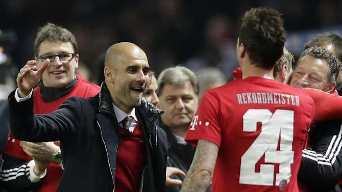 Bayern head coach Pep Guardiola of Spain, left, and player Mario Mandzukic of Croatia, right, celebrate winning the German soccer championship after the German Bundesliga soccer match between Hertha BSC Berlin and Bayern Munich in Berlin, Germany, Tuesday, March 25, 2014