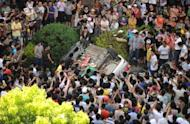 Protesters overturn a car near the local government office compound in Qidong, near the Chinese city of Shanghai, on July 28. Thousands of demonstrators protesting against alleged pollution from a paper factory in east China clashed with police Saturday, an AFP photographer said
