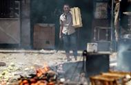 An Egyptian man uses a crate as a shield while holding a knife during clashes with anti-military protesters in the Abbassiya district of Cairo