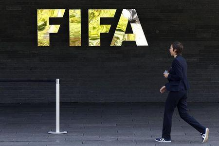 A staff walks past a logo of soccer's international governing body FIFA at their headquarters in Zurich