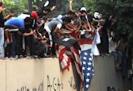 Egyptian protesters tear down the US flag at the US embassy in Cairo on September 11. The American ambassador to Libya, J. Christopher Stevens, and three officials were killed when a mob attacked the US consulate in the eastern city of Benghazi, the interior ministry said Wednesday, just hours after Islamists also stormed Washington's embassy in Cairo