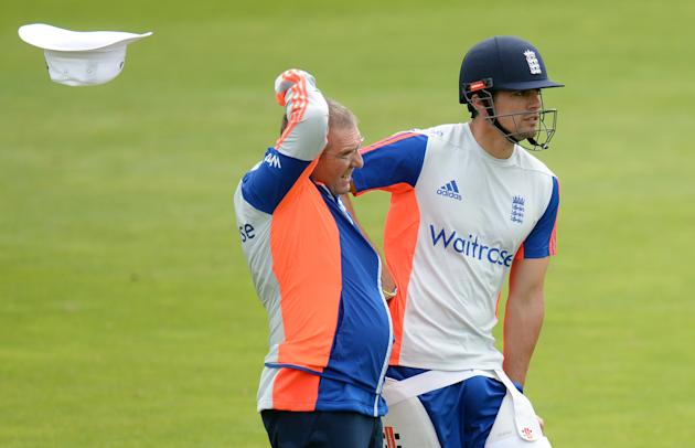 CRIC: England coach Trevor Bayliss has his hat blown away as he stands with captain Alastair Cook during a training session